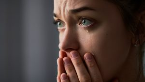 An image of a woman crying in feara, with her hand over her mouth