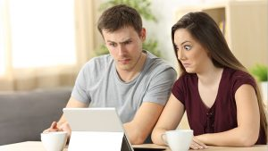An image of a confused and shocked couple looking at their tablet.