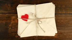 An image of a pile of love letters from a bove, tied with string and a small paper heart.
