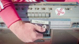 A Tracksuit cassette being put into a cassette player