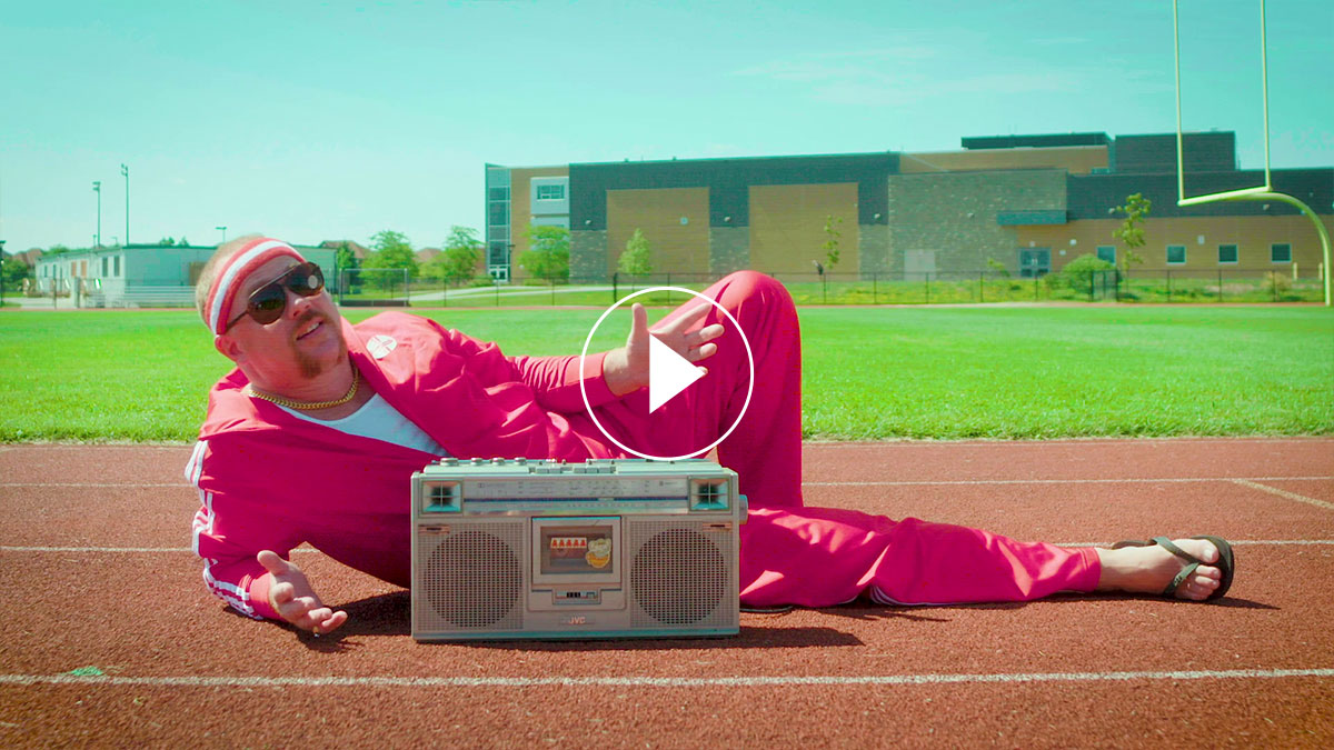 A man in a pink tracksuit lying on the floor behind a cassette player
